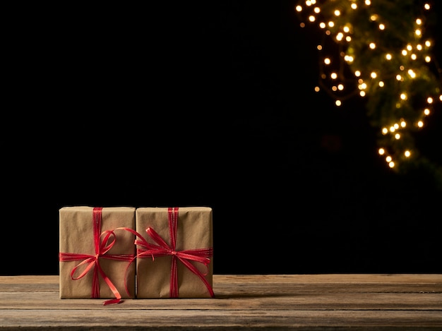 Рождественские подарочные коробки на деревянном столе на фоне размытых праздничных огней, место для текста