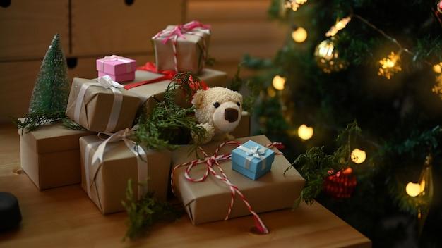 リビングルームのクリスマスツリーの近くの木製テーブルの上のクリスマスギフトボックス。