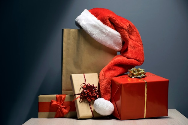 Christmas gift boxes in red and craft brown with santa hat over paper bag on dark
