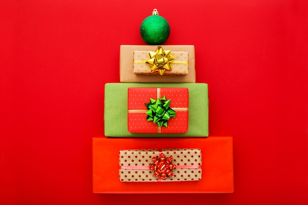 Christmas gift boxes in shape christmas tree red background. new year composition with copy space