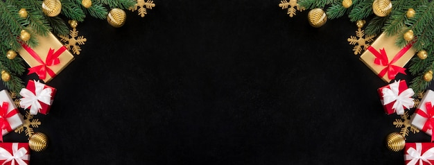 Christmas gift boxes and shiny golden decorating ornaments on blackboard background