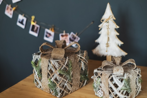 Christmas gift boxes on the table wooden surface with white decorative xmas tree and postcard garland on the wall