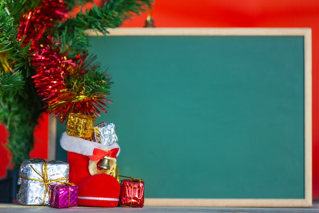 Christmas gift boxes in various colors placed in front of the green chalkboard