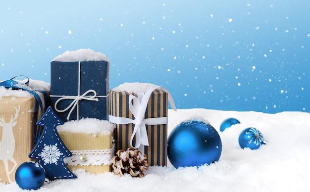 青いボールと雪で覆われた装飾が施されたクリスマスギフトボックス。コピースペースと冬のクリスマス水色の風景の背景。