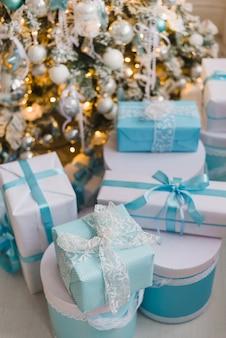 Рождественские подарочные коробки с синим бантом и огнями боке на деревянной поверхности
