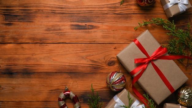 木製の背景にクリスマスの飾りの装飾が施されたクリスマスギフトボックス。