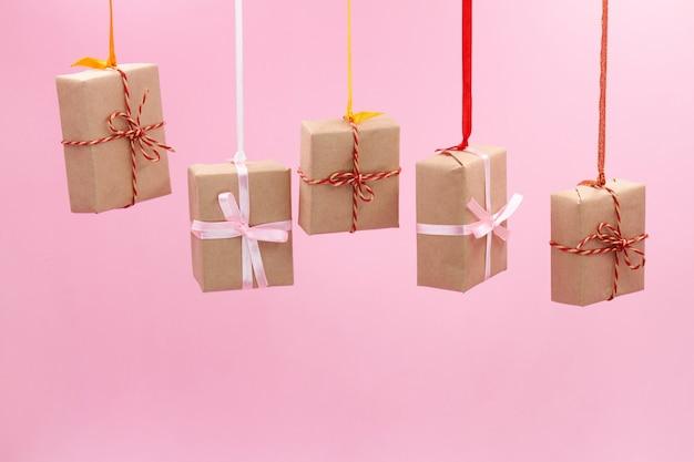 Рождественские подарочные коробки с разноцветными лентами висят на розовой стене