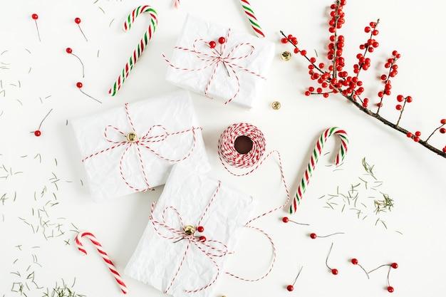 お祝いのキャンディー、赤い果実の枝、クリスマスロープのリール、白いテーブルの上のモミの針が付いているクリスマスギフトボックス。フラットレイ、上面図