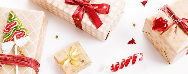 빨간색과 금색 리본과 사탕 지팡이가 있는 크리스마스 선물 상자, 크리스마스 구성, 화이트 보드에 배너, 배경. 평면도, 평면도, 복사 공간