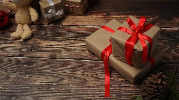 木製のテーブルに赤いリボンのクリスマスギフトボックス。
