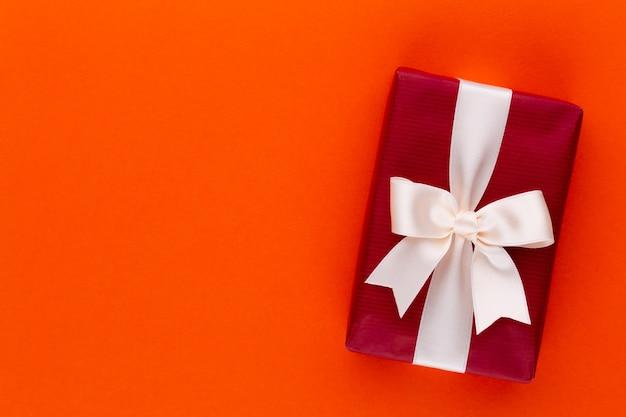Рождественские подарочные коробки с лентами на цветной столешнице.