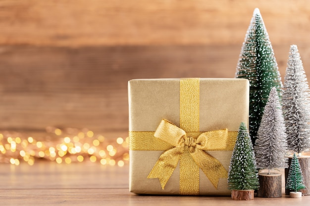 Christmas gift boxes with ribbons and tree on bokeh background.