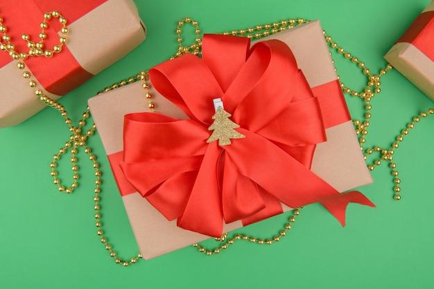 Рождественские подарочные коробки, завернутые в переработанную крафт-бумагу, с бантом из красной ленты на зеленом фоне