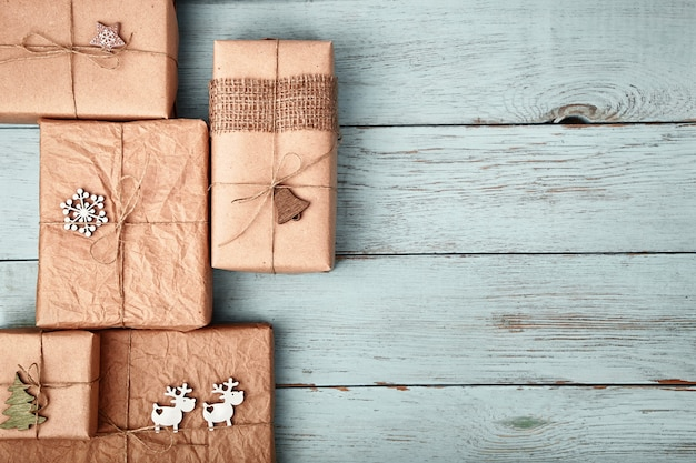 Christmas gift boxes wrapped in kraft paper on blue wooden table.