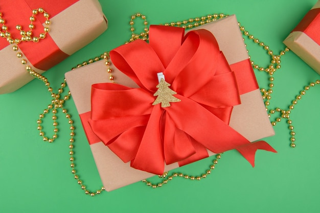 Christmas gift boxes wrapped in recycled kraft paper with red ribbon bow on a green background