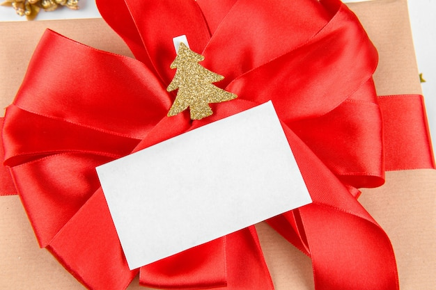 Christmas gift card. close up gift with red ribbon bow with gold christmas tree on clothespin with festive gold decoration.