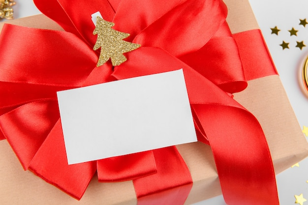 Christmas gift card mock up. close up gift with red ribbon bow with gold christmas tree on clothespin