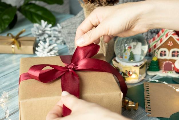 クリスマスプレゼント。おめでとうございます。伝統的な装飾が施されたギフトボックスを持っている女性のトップウィー。杖、モミの枝、モミの円錐形、およびベリーと木製のテーブル