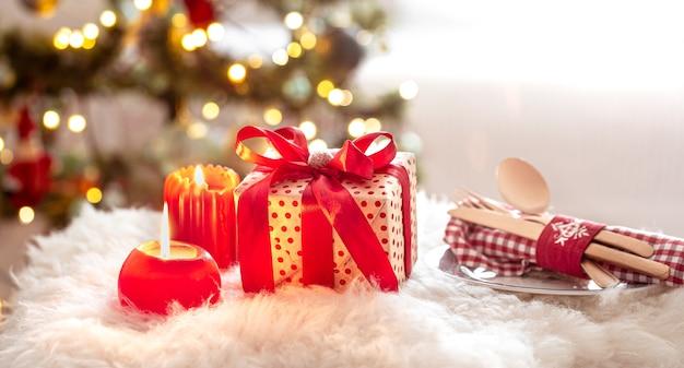 クリスマスプレゼント、カトラリーセット、ぼやけたボケ味の背景にキャンドルとプレートをクローズアップ。