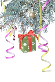 Christmas gift and decoration on fir tree branch isolated on white