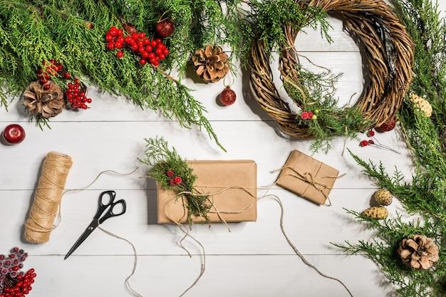 흰색 나무 배경에 수제 diy가 있는 크리스마스 선물 장식은 스스로 할 수 있습니다.