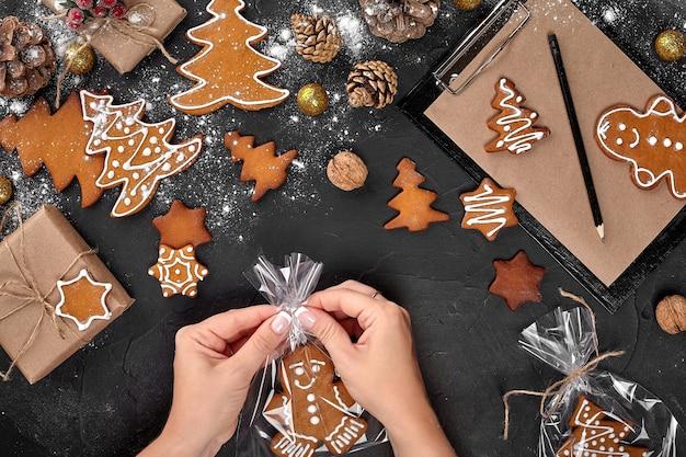 축제 포장 여성의 어두운 배경 비스킷에 크리스마스 선물 진저 브레드가 크리스마스를 포장하고 있습니다...