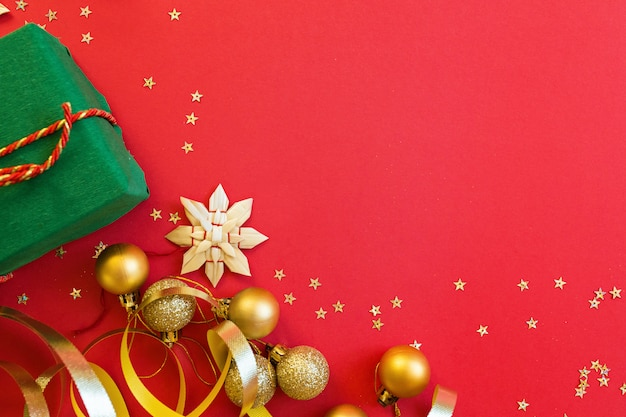 Christmas gift, golden toys lying on red background with confetti