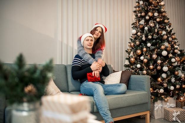 クリスマスプレゼント。家でクリスマスと新年の贈り物とサンタの帽子で幸せなカップル。