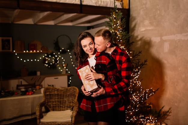 Рождественский подарок. счастливая пара с подарком на рождество и новый год дома. улыбаясь семьи вместе. рождественская елка