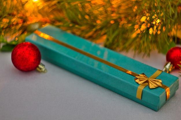 ゴールドのリボンが付いた青いボックスに入ったクリスマスプレゼントは、クリスマスツリーの下にあります。赤いクリスマスボールと美しいトウヒの枝。新年のテーマ