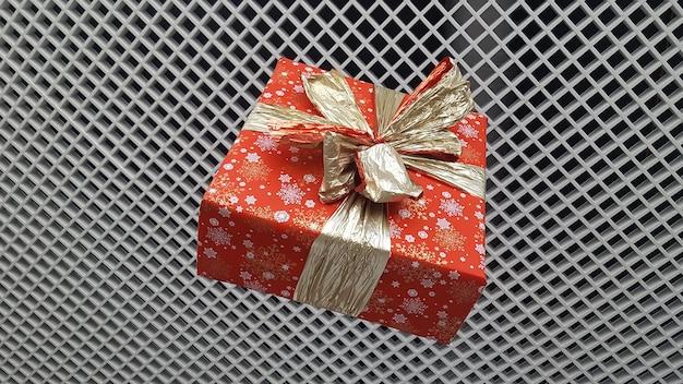 Рождественский подарок в яркой упаковке с красивым бантом на фоне решетки с мелкими ячейками. концепция новогоднего праздника.