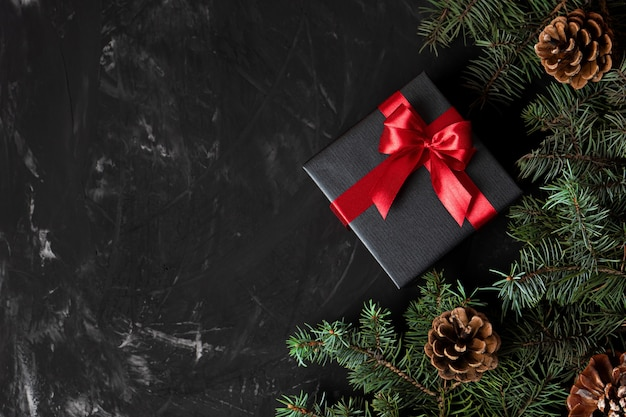 松の枝とテキストの場所と円錐形の赤で結ばれた黒い紙のクリスマスプレゼント。