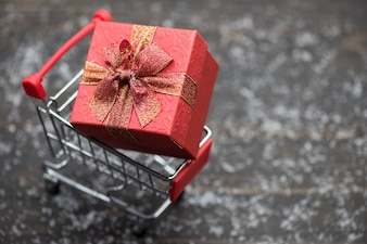 Christmas gift in cart over snow wood