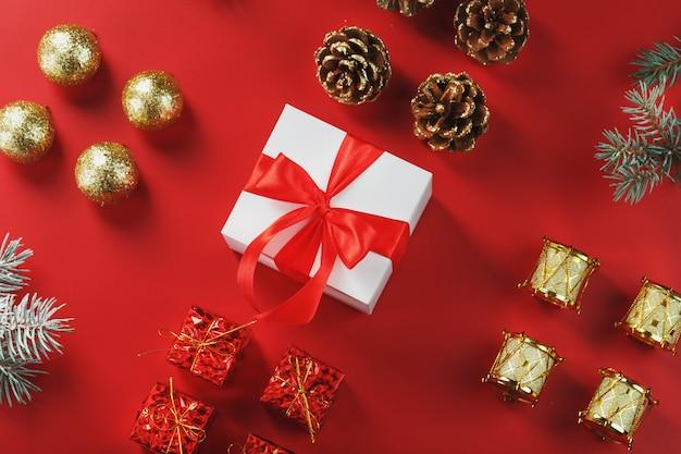 Рождественский подарок в виде белой коробки с красным бантом вокруг елочных игрушек. новогодняя композиция праздника.