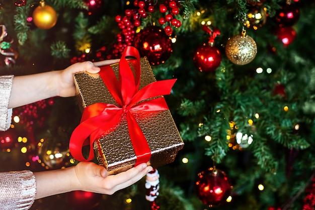 飾られたクリスマス ツリーの上の子供の手にクリスマス プレゼント