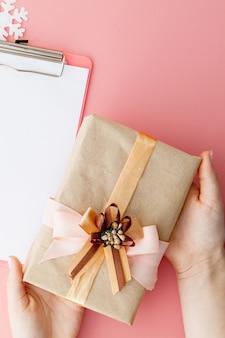 ピンクの背景に女性の手とノートブックのクリスマスプレゼント