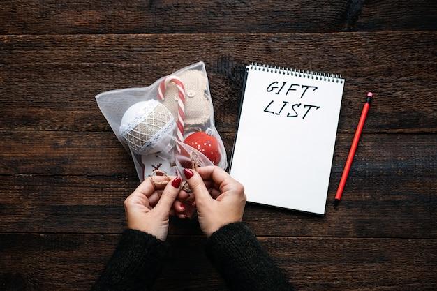 開いたメモ帳とテキストでギフトを追跡するクリスマスギフトリストクリスマスシーズンの女性の手