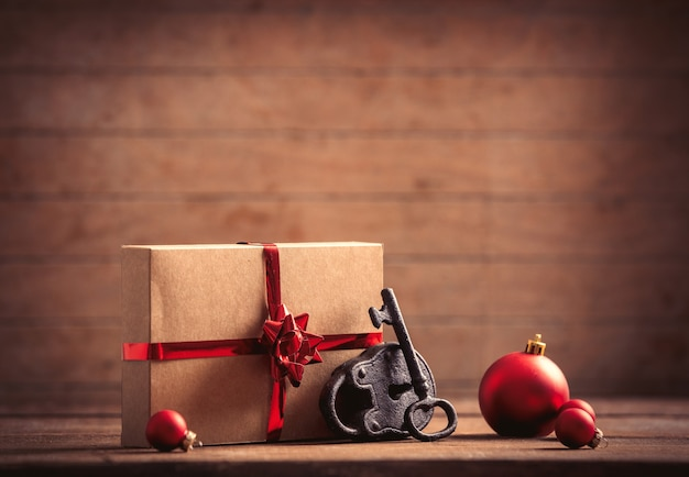 Christmas gift and lock with key on wooden table and background