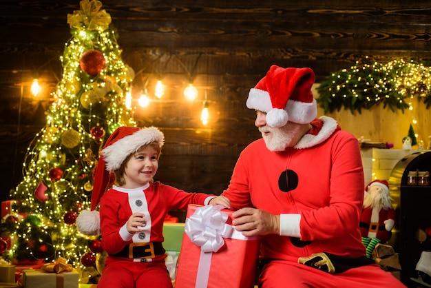 クリスマスプレゼントメリークリスマスクリスマスデコレーションとサンタの衣装で小さな子供の男の子を笑顔