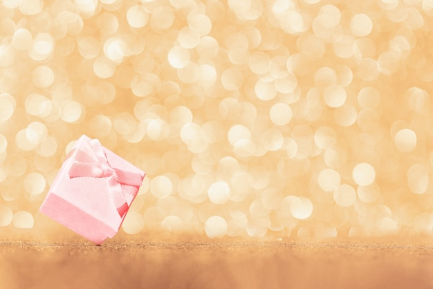 Christmas gift and new year abstract background with shiny gold glittered bokeh