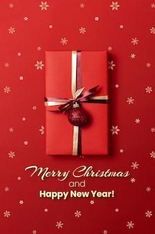 Рождественский подарок на красном фоне со снежинками
