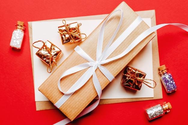 Рождественский подарок на красном новогоднем фоне