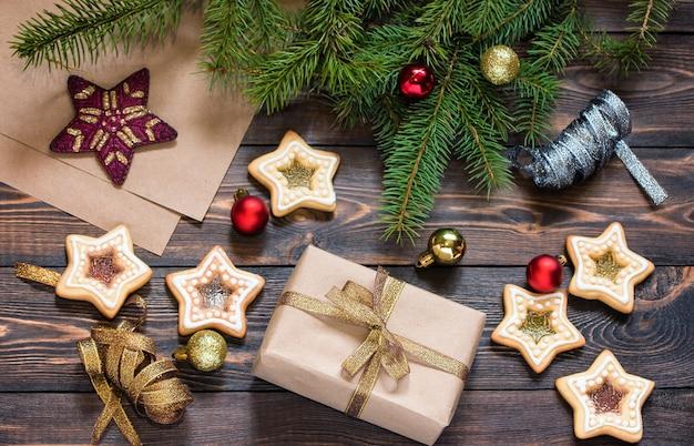 トウヒの枝の自家製クッキーとクリスマスツリーのおもちゃと木製の茶色のテーブルの上のクリスマスプレゼント