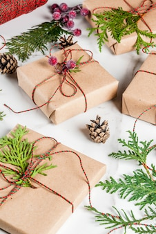 Рождественский подарок или подарочная коробка, завернутые в крафт-бумагу, украшенные ветками елки, сосновыми шишками, красными ягодами, на белом мраморном столе, copyspace