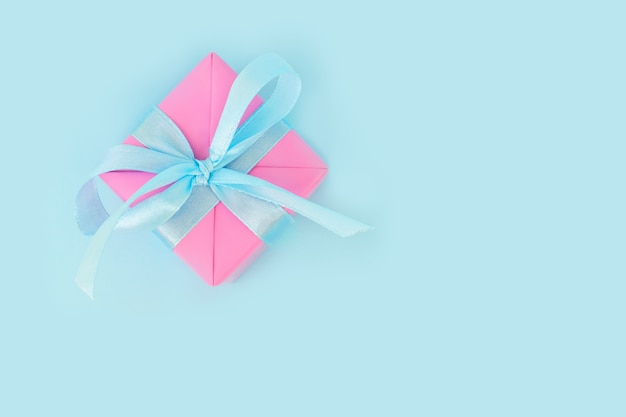 Christmas gift in a pink paper onblue  with place for text.