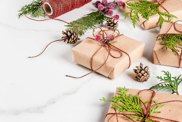 Christmas gift or present box wrapped in kraft paper, decorated with christmas tree branches, pine cones, red berries, on white marble table, copy space