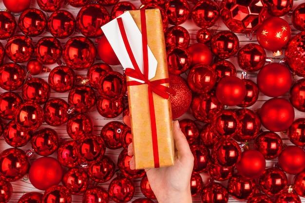 赤い光沢のあるつまらないものに囲まれたクリスマスプレゼント
