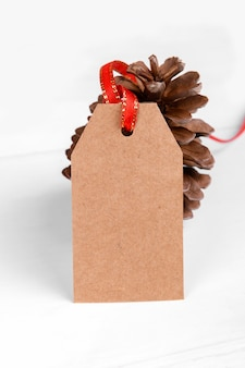 Christmas gift tag of craft paper present label with red ribbon and pine cone on white background.