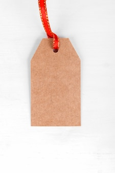 Christmas gift tag of craft paper present label with red ribbon on white background.