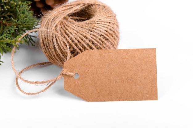 Christmas gift tag of craft paper present label with skein of rope and green fir branch on white background.